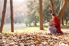 La lectura adentro de la naturaleza es mi afición, muchacha leyó un libro en las hojas caidas Fotos de archivo libres de regalías