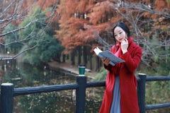 La lectura adentro de la naturaleza es mi afición, soporte de libro leído muchacha en el puente Fotos de archivo