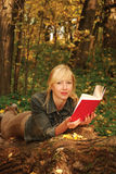 La lectura de la mujer rubia está poniendo en el árbol Imágenes de archivo libres de regalías