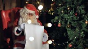La lectura de Papá Noel del primer pone letras cerca de la chimenea de la Navidad 4K almacen de video