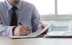 La lectura de trabajo del hombre de negocios documenta el gráfico financiero al suc del trabajo Imagen de archivo libre de regalías