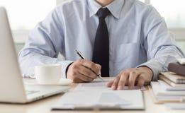 La lectura de trabajo del hombre de negocios documenta el gráfico financiero al suc del trabajo Imagen de archivo