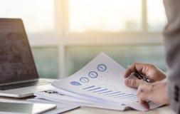 La lectura de trabajo del hombre de negocios documenta el gráfico financiero al suc del trabajo Imagenes de archivo