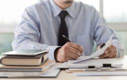 La lectura de trabajo del hombre de negocios documenta el gráfico financiero al suc del trabajo Imágenes de archivo libres de regalías