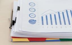 La lectura de trabajo del hombre de negocios documenta el gráfico financiero al suc del trabajo Fotos de archivo