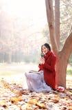 La lectura en naturaleza es mi afición, muchacha con el libro y té en el parque del otoño Imagenes de archivo