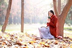 La lectura en naturaleza es mi afición, muchacha con el libro y té en el parque del otoño Fotos de archivo