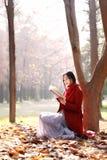 La lectura en naturaleza es mi afición, muchacha con el libro y té en el parque del otoño Imagen de archivo libre de regalías
