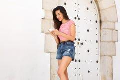 La lectura sonriente de la mujer joven manda un SMS en el teléfono móvil Imagen de archivo libre de regalías
