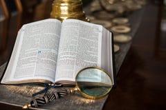 La lecture d'écriture sainte avec magnifient le verre Images libres de droits