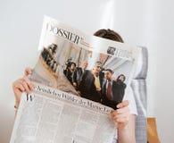 La lecture de femme meurent Zeit avec Emmanuel Macron et Marine Le Pen dessus Image stock