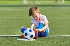 La legatura di calcio di calcio del ragazzo lo merletta stivali su erba Immagine Stock Libera da Diritti