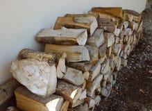 La legna da ardere asciutta pone ordinatamente sulla terra vicino alla parete beige fotografia stock libera da diritti