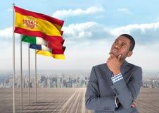 la lengua principal señala por medio de una bandera cerca del hombre de negocios joven que piensa con la ciudad detrás Imagenes de archivo