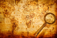 La lente d'ingrandimento d'annata si trova su una mappa di mondo antica Fotografie Stock Libere da Diritti