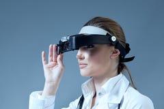 La lente d'ingrandimento da portare del giovane medico femminile dota Immagine Stock Libera da Diritti