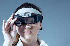 La lente d'ingrandimento da portare del medico femminile giovane dota Immagine Stock