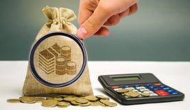 La lente d'ingrandimento esamina la borsa dei soldi con le monete e un calcolatore Calcolo di profitto ed analisi di reddito Tass immagini stock