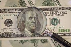 La lente d'ingrandimento si trova su cento banconote in dollari Immagine Stock