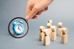 La lente d'ingrandimento sta esaminando l'orologio blu Folla degli sguardi della gente all'orologio La gente dell'attenzione ? in immagine stock