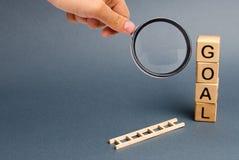 La lente d'ingrandimento sta esaminando una torre dei cubi con uno scopo dell'iscrizione e una scala caduta Strumento per success immagini stock libere da diritti