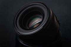 La lente de la foto en un fondo oscuro con un punto Fotos de archivo libres de regalías