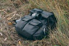La lentille se trouve sur un sac à dos dans l'herbe verte Photos stock