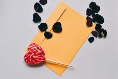 La letra de amor del día del ` s de la tarjeta del día de San Valentín con el caramelo rojo formó el corazón Fotografía de archivo libre de regalías
