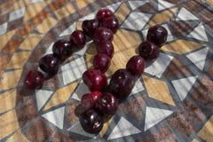 La letra N hizo con los cherrys para formar una letra del alfabeto con las frutas Fotos de archivo