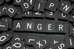 La letra negra teja el deletreo de la palabra y del x22; anger& x22; fotografía de archivo libre de regalías