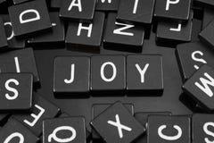 La letra negra teja el deletreo de la palabra y del x22; joy& x22; Foto de archivo libre de regalías