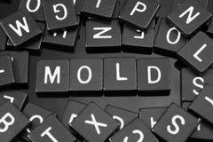 La letra negra teja el deletreo de la palabra y del x22; mold& x22; fotos de archivo