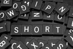 La letra negra teja el deletreo de la palabra y del x22; short& x22; fotos de archivo libres de regalías