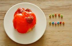 La lettera ha sistemato la parola felice di domenica ed il dolce della fragola sul piatto Immagini Stock