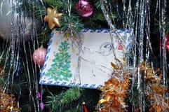 La lettera per Santa Claus si trova nei rami dell'abete rosso Fotografia Stock