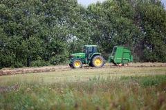 La Lettonia - 6 agosto 2017: Trattore di John Deere che raccoglie fieno di erba asciutta dopo la falciatura sul campo del prato a Immagine Stock