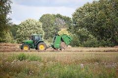 La Lettonia - 6 agosto 2017: Trattore di John Deere che raccoglie fieno di erba asciutta dopo la falciatura sul campo del prato a Fotografie Stock Libere da Diritti
