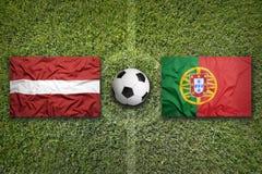 La Lettonia contro Bandiere del Portogallo sul campo di calcio Fotografia Stock Libera da Diritti