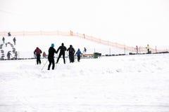 La Lettonia, Riga - 17 febbraio 2017: Skiin degli sport invernali della gente nell'itinerario della pista della neve Fotografia Stock Libera da Diritti