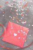La lettre d'amour accroche sur la corde et les coeurs a sur un fond foncé Photographie stock libre de droits
