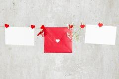 La lettre d'amour accroche sur la corde et une fleur sur un fond clair Photo stock