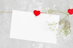 La lettre d'amour accroche sur la corde et une fleur sur un fond clair Photographie stock libre de droits