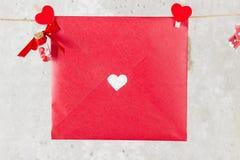 La lettre d'amour accroche sur la corde et une fleur sur un fond clair Photos stock