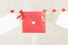 La lettre d'amour accroche sur la corde et une fleur sur un fond clair Images libres de droits
