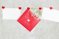 La lettre d'amour accroche sur la corde et une fleur sur un fond clair Image libre de droits
