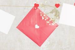 La lettre d'amour accroche sur la corde et une fleur sur un fond clair Photographie stock