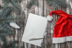 La lettre de Joyeux Noël avec le chapeau du ` s de Santa et le sapin vert s'embranche sur le vieux fond en bois Photo stock