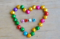 La lettre en plastique s'chargent de la cloche d'amour et de coeur sur le conseil en bois Photo libre de droits