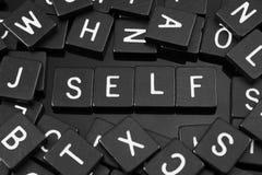 La lettre noire couvre de tuiles orthographier le mot et le x22 ; self& x22 ; image stock