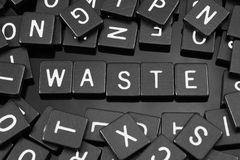 La lettre noire couvre de tuiles orthographier le mot et le x22 ; waste& x22 ; images stock